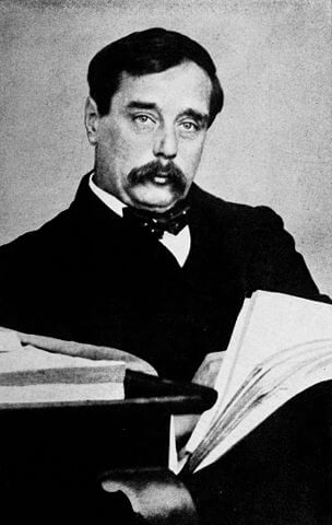 Science-fictiion author H.G. Wells sites with a book in his arms.